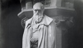 A stone statue of a bearded man, hands crossed at his front, shoulders draped in a cloak