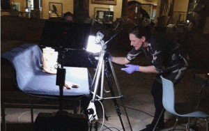 events manager Laura is seen leaning over a lighting set-up that is shedding light on a table with specimens.