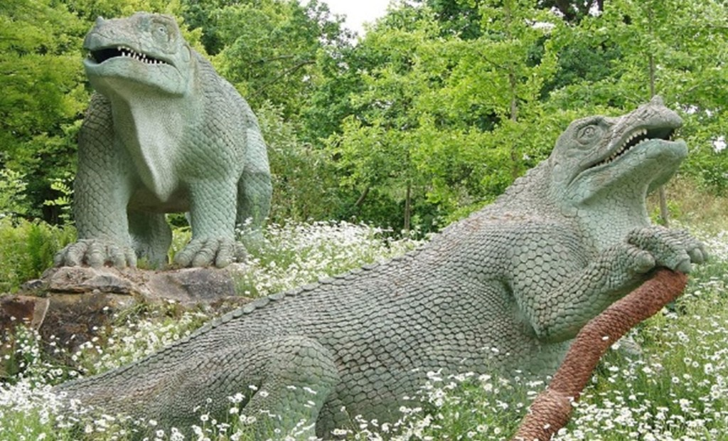 Two green dinosaur models surrounded by trees and meadow flowers