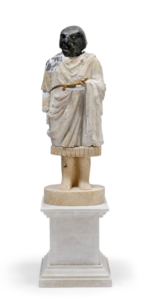 Statue of a robed figure standing on a plinth and holding a golden lizard-like reptile in one hand