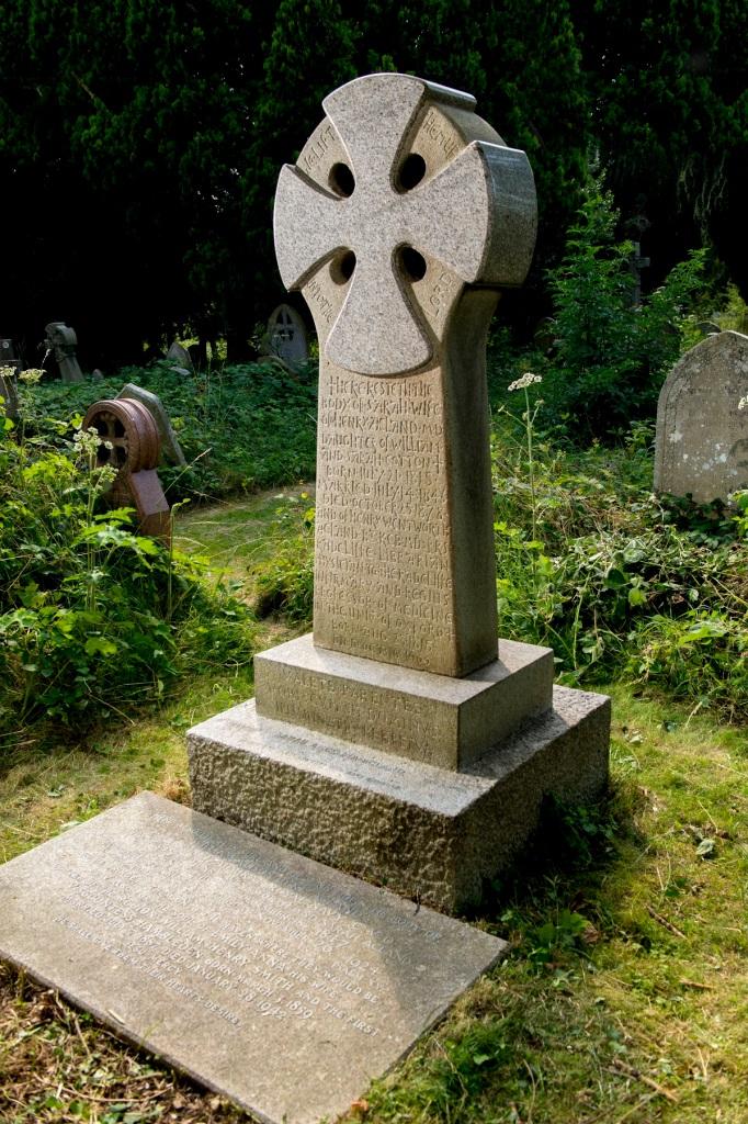 Headstone in grass cemetery