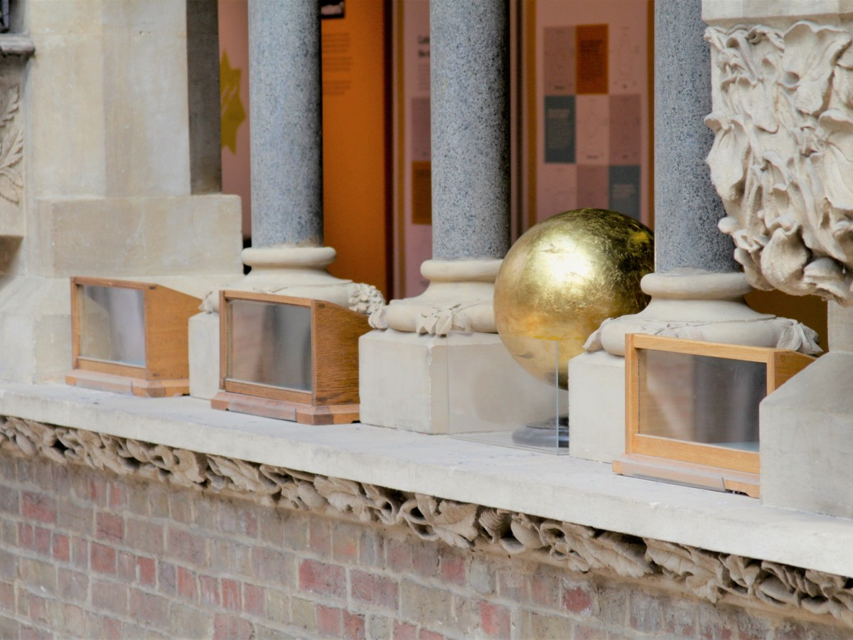 A golden sphere sitting on a stone balcony between stone columns and carvings